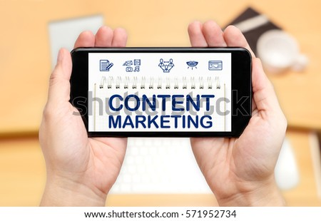 Watching two hand holding mobile phone with Content marketing word on screen and blur desk office background,Digital content concept. #571952734