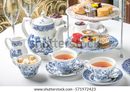 old school style tea at five afternoon service sandwich set cake sweet traditional table hotel cheesecake sugar pot blue china cup  Royalty-Free Stock Photo #571972423