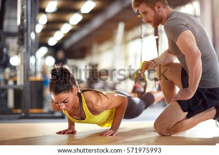 Fitness instructor with girl on training in fitness center #571975993