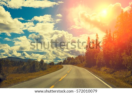 Mountain road at sunset with cloudy sky #572010079