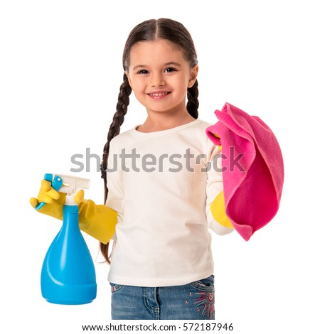 Cute little girl in protective gloves is holding a detergent and a duster, looking at camera and smiling, isolated on white #572187946