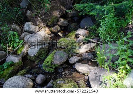 Flowing water through rocks #572221543