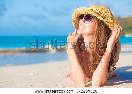 woman in bikini and straw hat lying on tropical beach #572259820