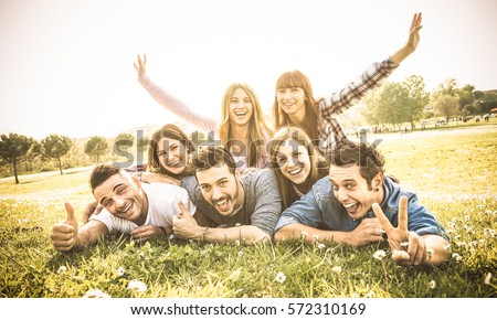 Friends group having fun together with self portrait on grass meadow - Friendship youth concept with young happy people at picnic camping outdoor - Warm vintage filter with backlight contrast sunshine #572310169