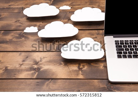 Cloud computing concept laptop close up with white clouds coming out of the computer indicating online storage and internet connection. #572315812