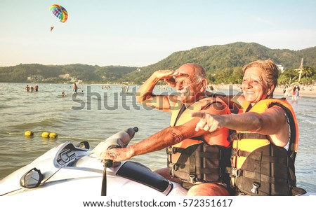 Senior happy couple having fun on jet ski at beach island hopping tour - Active elderly and travel concept around the world with retired people riding water scooter jetski - Warm vintage vivid filter