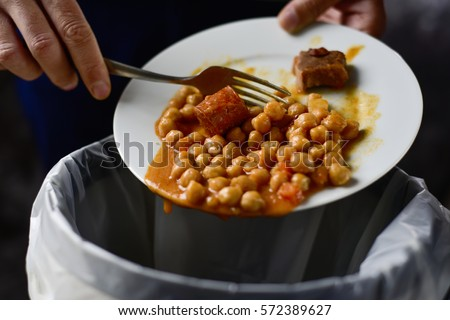closeup of a young caucasian man throwing the leftover of a plate of chickpea stew to the trash bin #572389627