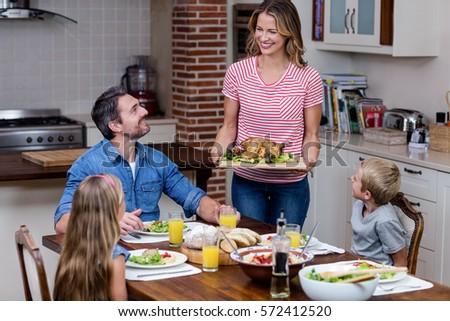 Woman serving food to her family in the kitchen at home #572412520