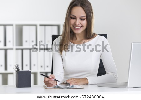 Front view of a smiling blond woman wearing white clothes and writing in her clipboard while sitting at her workplace. #572430004