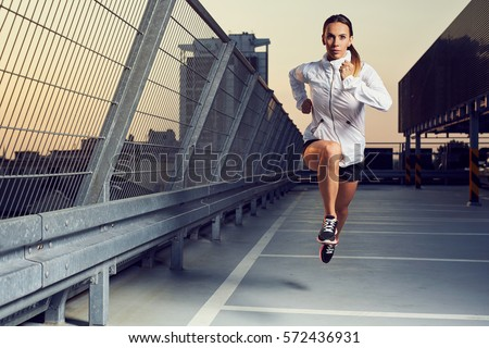 Picture of young woman sprinting on the rooftop parking garage