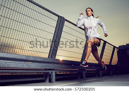 Athletic woman running during sunset on rooftop of parking, garage #572500201