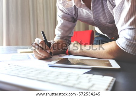 Male manager putting his ideas and writing business plan at workplace with warm fall colors. soft-focus in the background. over light #572534245