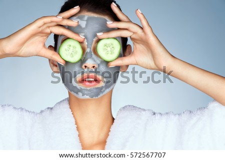 Young woman with a clay mask. Photo of attractive young woman covering her eyes with cucumbers on a blue background. Grooming himself #572567707