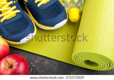 Yoga mat, sport shoes, apples, bottle of water on dark background. Concept healthy lifestyle, healthy eating, sport and diet. Sport equipment. Copy space #572573029
