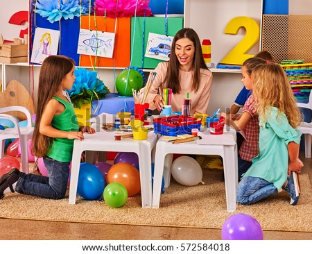 Children painting and drawing in kids club. Art lesson in primary school. Kindergarten teacher who smiling help small students. Kid boy coloring picture on table in class. Balloons on floor.