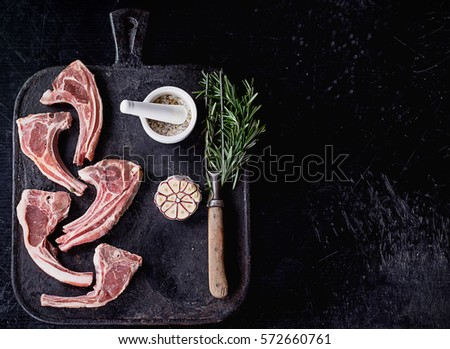 Raw Lamb Ribs on a rustic metal board with rosemary, garlic salt and pepper. Black Background. Top View #572660761