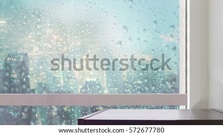 black wooden table at glass window of raining at city night view