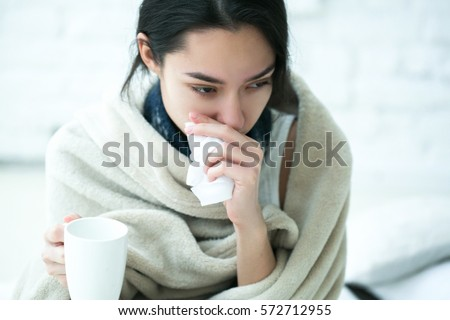 Young girl sick in bed with temperature drinks hot  Royalty-Free Stock Photo #572712955