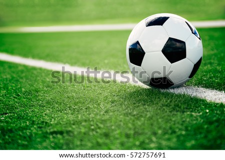 Traditional soccer ball on soccer field Royalty-Free Stock Photo #572757691