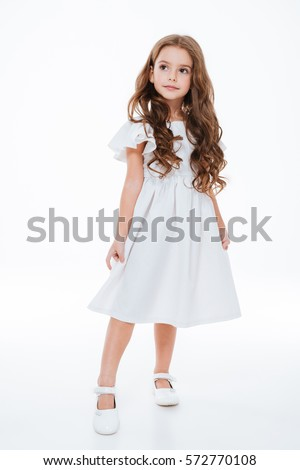 Full length of beautiful little girl in dress standing and posing over white background #572770108