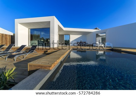 Modern house with garden swimming pool and wooden deck #572784286