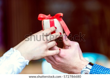 Hands of a Man and Woman Holding Present #572786680