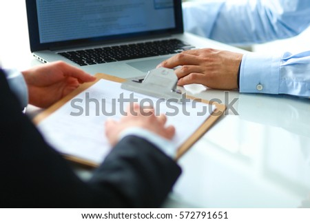 Businesspeople sitting on the desk in office #572791651