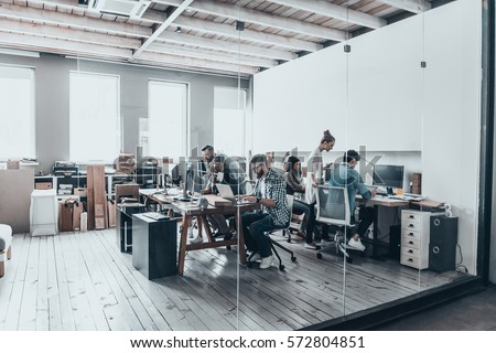 Successful business team.  Group of young business people working and communicating together while sitting at their working places in office  #572804851