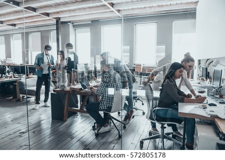 Successful team at work. Group of young business people working and communicating together in creative office Royalty-Free Stock Photo #572805178