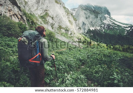Man traveler with backpack hiking Travel Lifestyle concept adventure active  summer vacations outdoor rocky mountains on background Royalty-Free Stock Photo #572884981