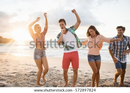 Friends having fun and dancing at the beach #572897824