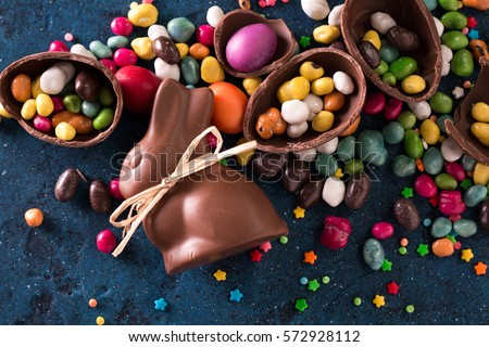 Delicious chocolate easter eggs ,bunny and sweets on dark blue background Royalty-Free Stock Photo #572928112