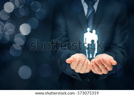 Family life insurance, family services and supporting families concepts. Businessman with protective gesture and silhouette representing young insured family. #573075319