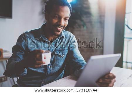 Happy young African man reading world news by digital tablet while sitting at the table on a sunny morning.Concept of coworking people working home.Blurred background,flare effect #573110944