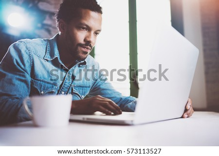 Pensive bearded African man working on laptop while spending time at home.Concept of young business people using mobile devices.Blurred background, crop. #573113527