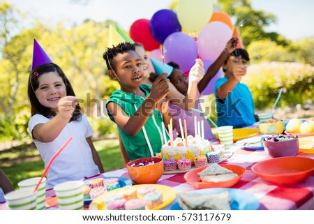 Cute children smiling and having fun during a birthday party on a park #573117679
