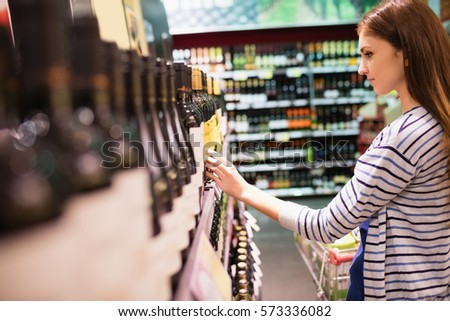 Young woman selecting wine in the supermarket #573336082