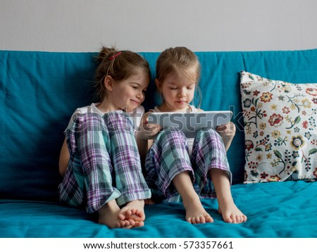 children play on the tablet and watch cartoons