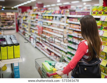 Rear view of woman shopping at the supermarket #573361678