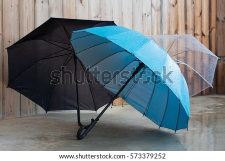Umbrellas on a concrete floor in front of a wooden home in a rainy day. #573379252
