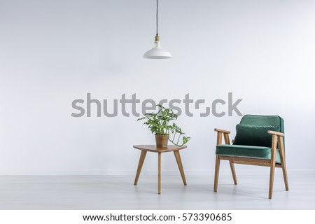 White room with green armchair, small table and plant Royalty-Free Stock Photo #573390685