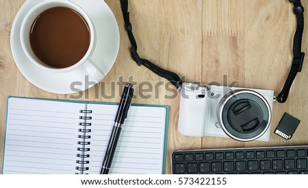 Coffee cup and blank opened notebook with pen, Mirrorless camera with memory card and keyboard on wooden table, Writing idea concept, Flat lay, Table top view #573422155