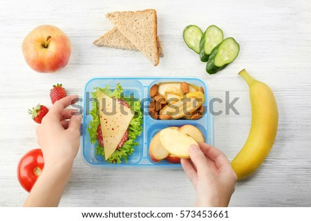 Mother putting food in lunch box, top view #573453661