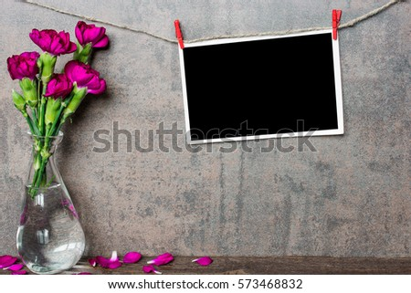 mock up blank photo frame hanging on rope with purple carnation flowers in vase on wooden background with copy space