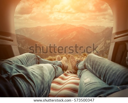 Couple in car. Blonde female and male in jeans in them car looking on beautiful mountains view at autumn day. #573500347