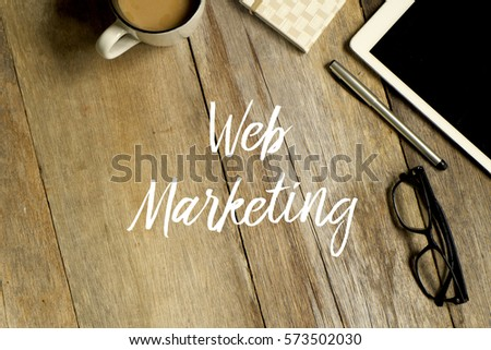 Business concept. Top view of tablet, glasses. notebook pen and a cup of coffee with WEB MARKETING written on wooden background. #573502030