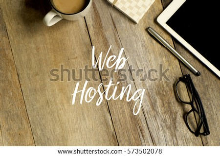 Business concept. Top view of tablet, glasses. notebook pen and a cup of coffee with WEB HOSTING written on wooden background. #573502078