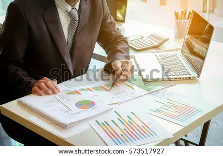 Close up of hand of business man working document and laptop in office morning light. business concept. #573517927