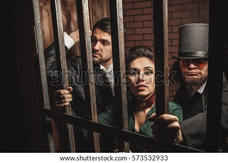 Two gentlemen and a lady behind bars in the prison. #573532933