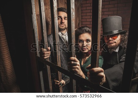 Two gentlemen and a lady behind bars in the prison. #573532966